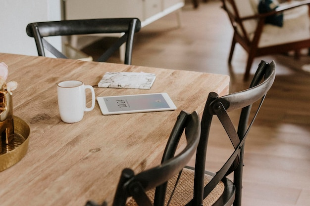 Tableta digital y un cuaderno de textura de mármol en una mesa de comedor de madera