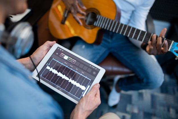 Tableta digital con formas de onda de sonido en su pantalla sostenida por un joven músico contemporáneo durante el proceso de grabación