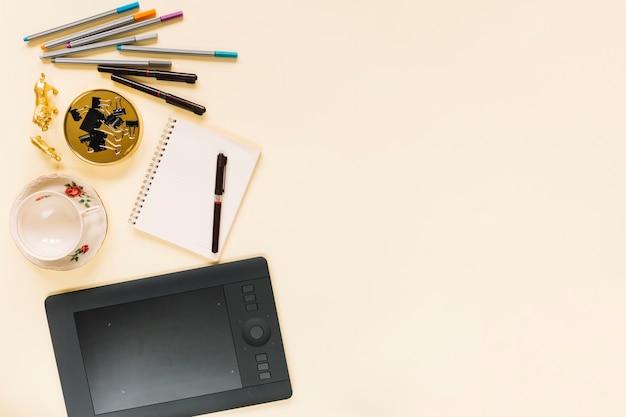Tableta digital gráfica con rotulador sobre cuaderno espiral y taza de cerámica vacía sobre fondo crema