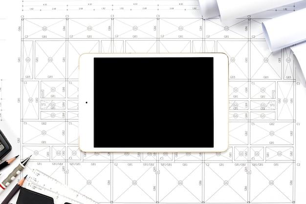 Tableta digital con herramientas de dibujos sobre fondo abstracto de dibujos de ingeniería.