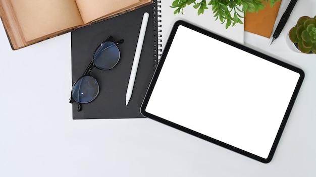 Tableta digital, lápiz óptico, gafas, cuaderno y planta de interior en el escritorio de oficina blanco.