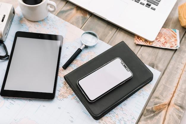 Tableta digital; lupa y diario en el mapa sobre la mesa de madera