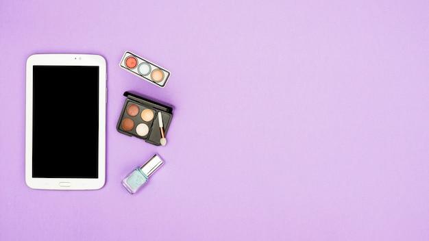 Tableta digital con paleta de sombra de ojos y botella de esmalte de uñas sobre fondo morado