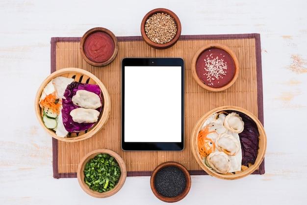 Tableta digital de pantalla blanca en blanco envolvente con salsa; cebollino y semillas de sésamo sobre mantel sobre fondo de textura