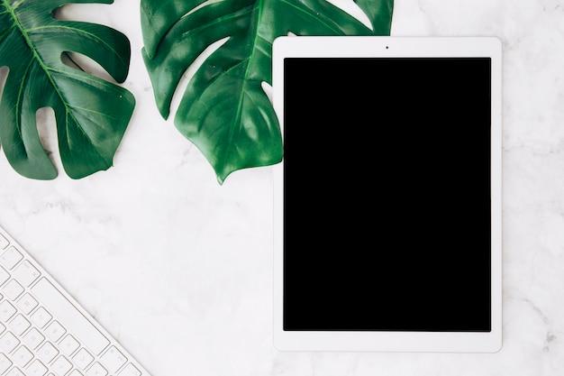 Tableta digital de pantalla en blanco con hojas de monstera y teclado en el escritorio de mármol blanco