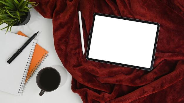 Tableta digital con pantalla en blanco, lápiz óptico, taza de café y cuaderno en manta roja.