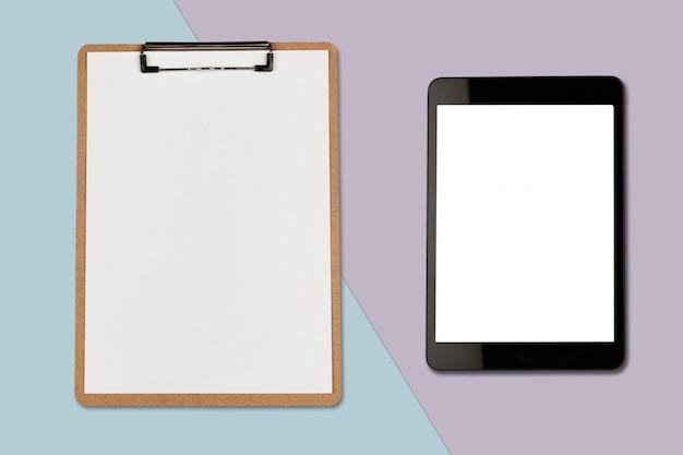 Tableta digital con pantalla en blanco y portapapeles sobre fondo de color pastel, foto plana