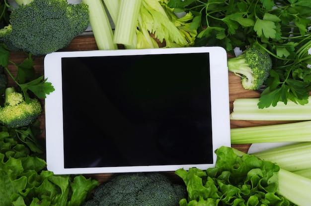 Tableta digital con pantalla en blanco rodeada de verduras, concepto de comida saludable