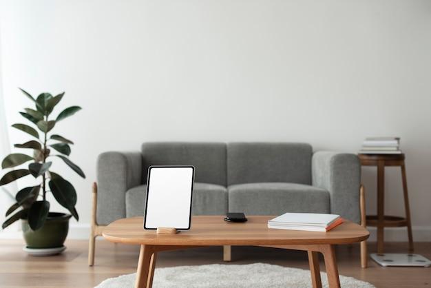 Tableta digital con pantalla en blanco sobre mesa de madera