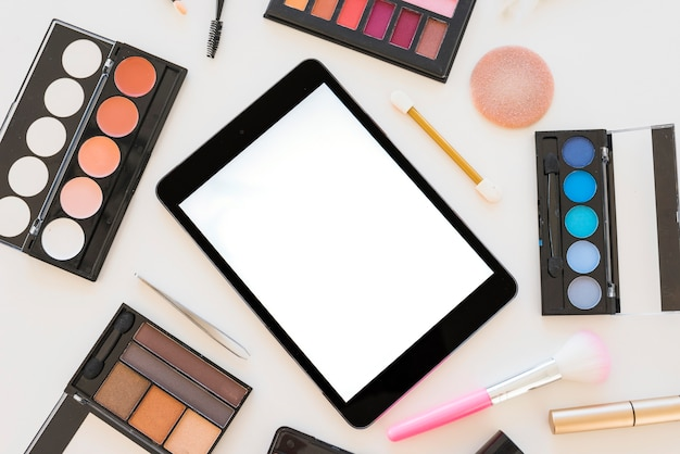 Tableta digital con pantalla en blanco y varios productos cosméticos sobre fondo blanco