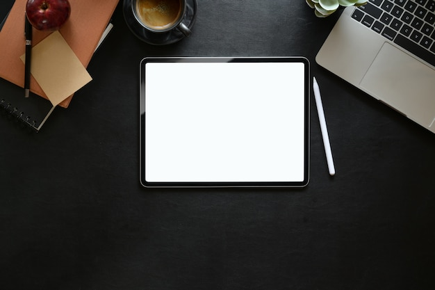 Tableta digital de la pantalla en blanco de la vista superior en lugar de trabajo del estudio