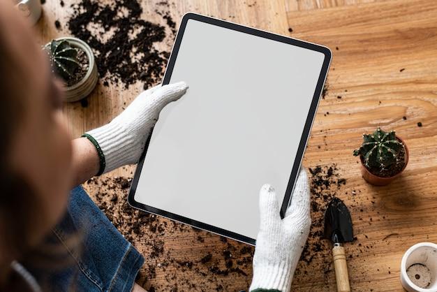 Tableta digital con pantalla vacía en la mano de un jardinero