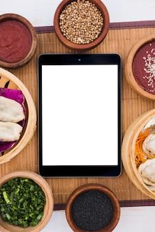Tableta digital rodeada de vaporeras; cebolleta; semillas de sésamo y semillas de cilantro en mantel