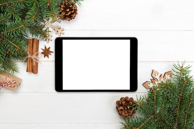 Tableta digital simulada con decoraciones de superficie de madera rústica de navidad para la presentación de la aplicación