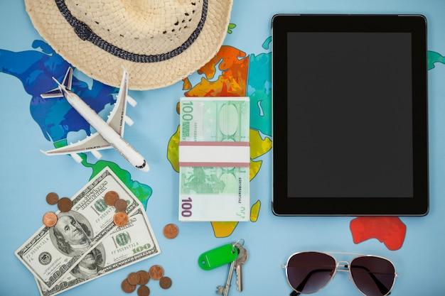 Tableta digital, sombrero, gafas de sol, modelo dólar y avión