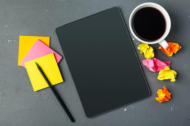 Tableta digital y taza de café en el escritorio de madera.