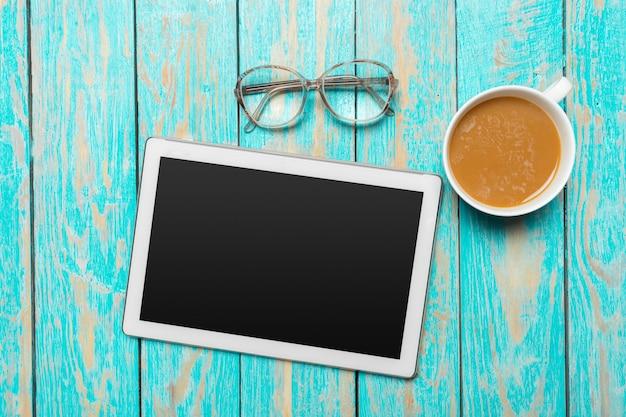 Tableta digital y taza de café en mesa de madera