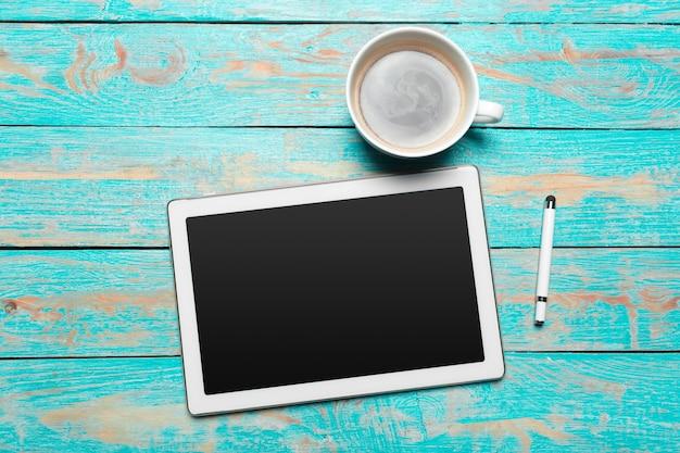 Tableta digital y taza de café en la mesa de madera
