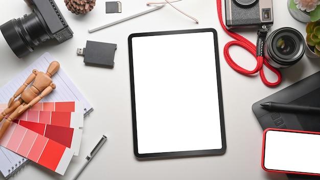 Tableta digital, teléfono inteligente, cámara y suministros en mesa blanca.