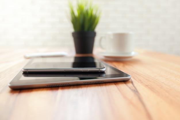 Tableta digital y teléfono inteligente en mesa de madera