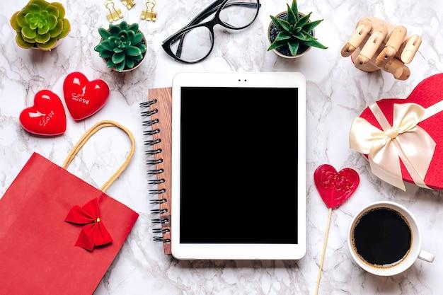 Tableta para elegir regalos, compra, taza de café, tarjeta de débito, caja, bolso, dos corazones en la mesa de mármol