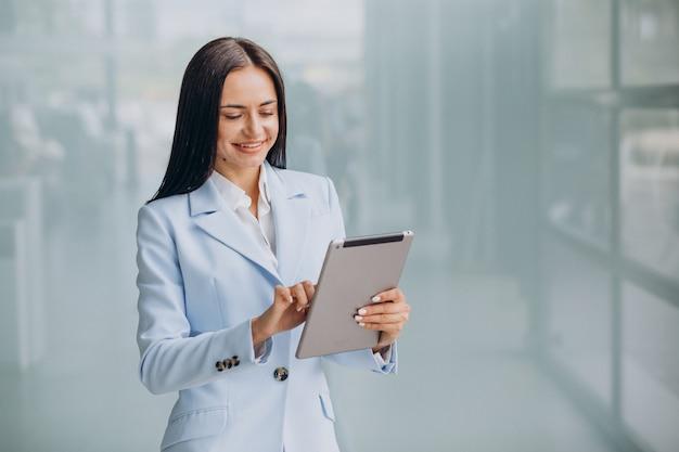 Tableta de explotación de isoled de mujer de negocios joven