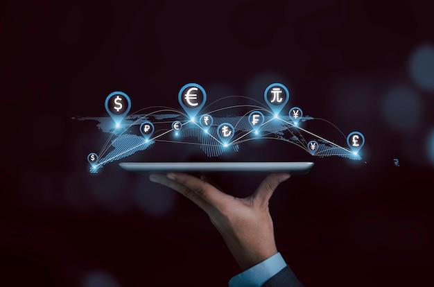 Tableta de explotación de mano de empresario con línea de conexión de mapa del mundo virtual y moneda global, transferencia de tecnología y concepto de cambio de moneda.