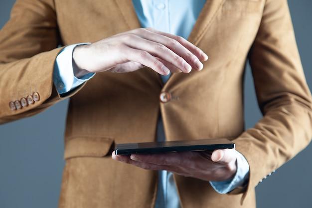 Tableta de explotación de mano de hombre sobre fondo gris