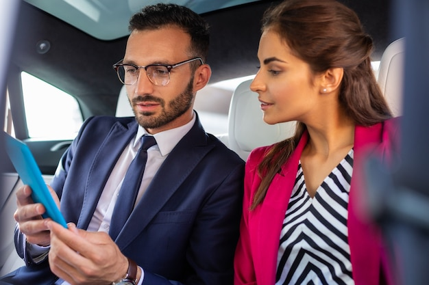 Tableta de explotación del marido. marido sosteniendo la mesa mientras está sentado en el coche cerca de su hermosa esposa de moda