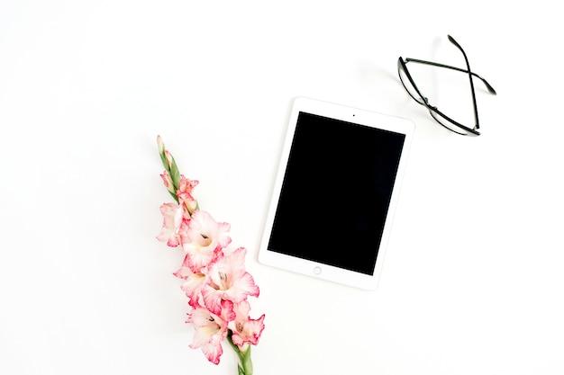 Tableta, flor de gladiolo y vasos. concepto de negocio de mujeres