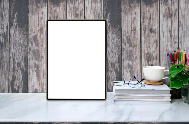 Tableta y fuentes de la pantalla en blanco de la maqueta en la tabla de mármol con la pared de madera vieja.