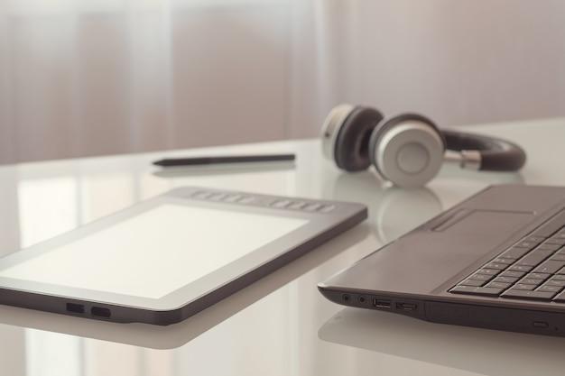 Una tableta gráfica, computadora portátil, auriculares están acostados sobre una mesa de vidrio.