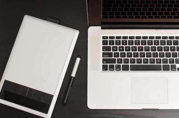 Tableta gráfica con un lápiz, un portátil en la mesa de madera negra, primer plano