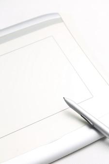 Tableta gráfica y lápiz sensible a la presión sobre fondo blanco