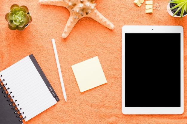 Tableta con herramientas de oficina sobre fondo claro