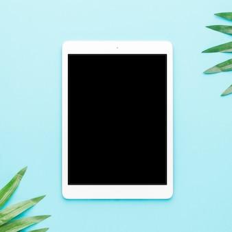 Tableta con hojas tropicales sobre fondo claro