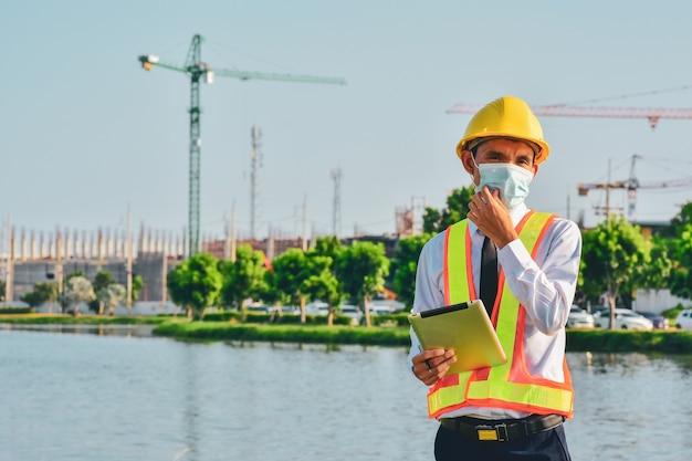 Tableta de ingeniero de arquitectura trabaja duro en la construcción del sitio, día del trabajo