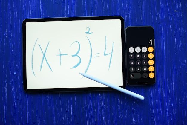 Tableta con la inscripción de la ecuación matemática con lápiz y teléfono -calculadora en el cuadro azul