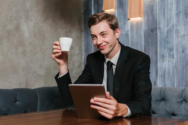 Tableta joven de la tenencia del hombre de negocios