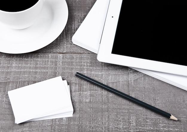 Tableta con lápiz, tarjetas de papel y café en escritorio de oficina