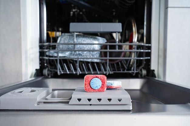 Tableta de lavavajillas multicolor en un recipiente de plástico para lavar platos.