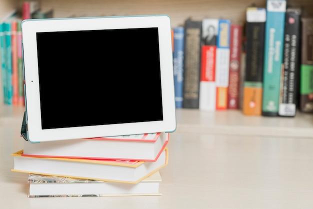 Tableta y libros cerca de estantería