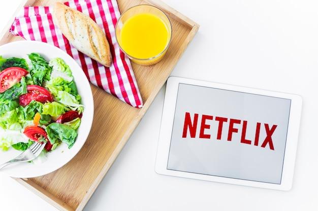 Tableta con el logo de netflix cerca de alimentos saludables.