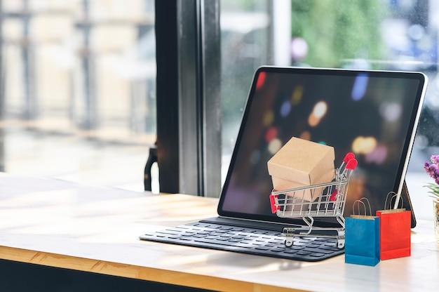 Tableta de maqueta con carrito de la compra y bolsa de papel en la mesa de madera.