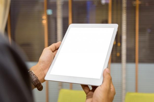 La tableta de la maqueta en hombre de negocios da la exhibición vacía en la tabla casera con el fondo de la falta de definición