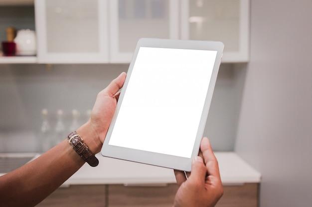 La tableta de la maqueta en hombre de negocios da la exhibición vacía en la tabla casera.