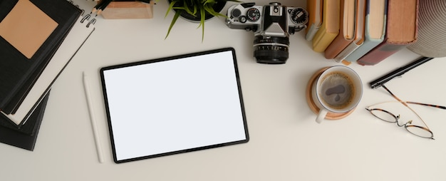 Tableta de maqueta en mesa de trabajo blanca con taza de café, vasos, cuadernos, cámara de libros y maceta