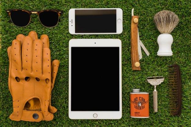 Tableta y móvil sobre superficie de hierba para el día del padre