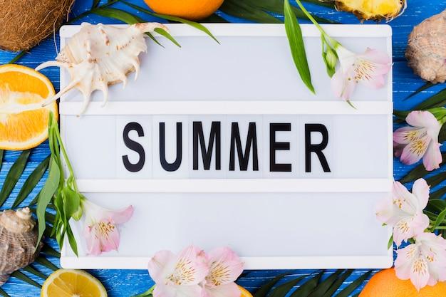 Tableta con palabra de verano entre hojas de plantas cerca de flores y frutas