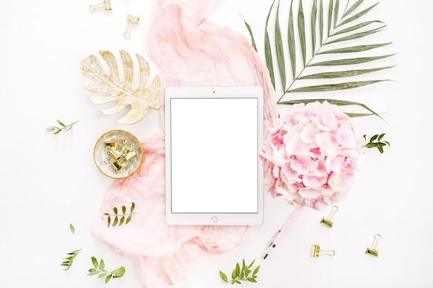 Tableta de pantalla en blanco, flores de hortensia rosa, hoja de palma y accesorios en superficie blanca